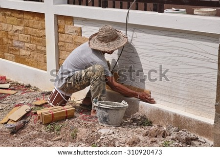 Worker Tile the Wall - stock photo