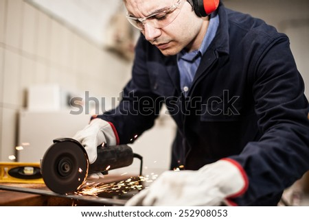 Worker using a grinding machine on a metal plate - stock photo