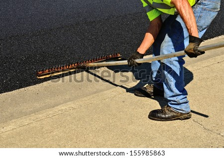 Worker using a rake to push excess asphalt off of concrete curbing on a repaving construction project - stock photo