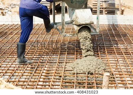 Worker using backhoe to lift concrete bucket in construction site - stock photo