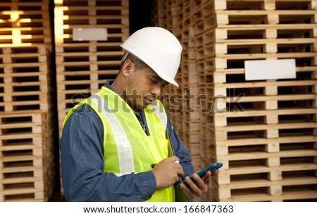 worker using smart phone in warehouse pallet - stock photo
