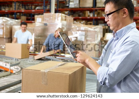 Worker Using Tablet Computer In Distribution Warehouse - stock photo