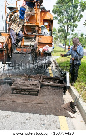Worker water on truck  Para Slurry Seal and ready to pave Asphalt road renovation - stock photo