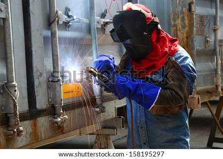 Worker welder container box maintenance in location - stock photo