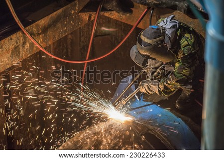 Worker welding the pipe part by manual - stock photo