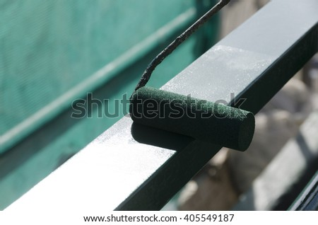 worker while painting a railing with a roller - stock photo