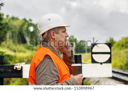 Worker with a coffee and cell phone on the railway in summer - stock photo