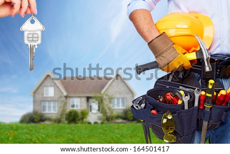 Worker with a diy tool belt over construction background - stock photo