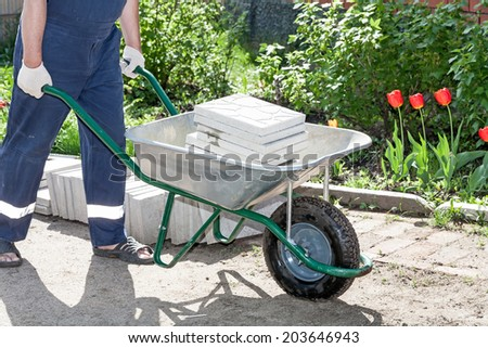 Worker with a wheelbarrow loaded with paving slabs.  - stock photo