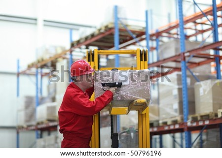 worker with bar code reader working in warehouse - stock photo