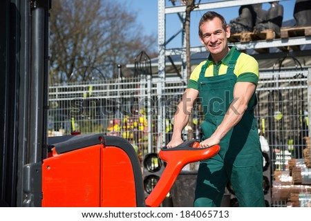 Worker with forklift at warehouse or storehouse - stock photo