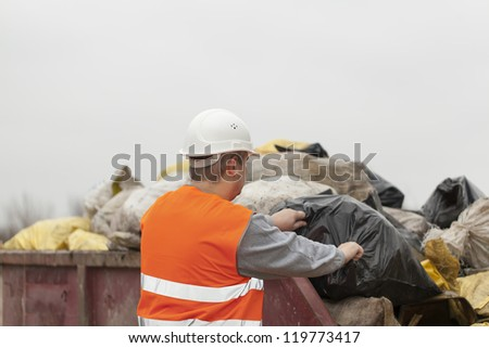 Worker with garbage and debris bags to a container - stock photo