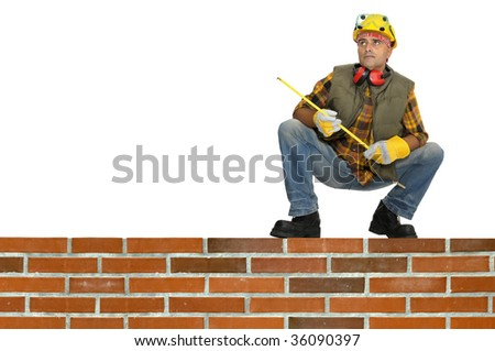 Worker with hat and earphones and brick wall isolated in white - stock photo