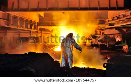 worker with hot steel in plant - stock photo