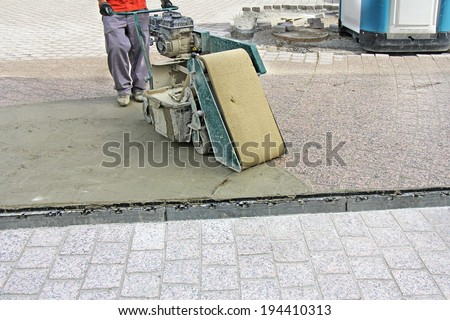 Worker with machine, grouting compound street paved with bricks - stock photo
