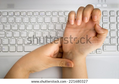 worker with pain on the wrist by the hard work at the office  - stock photo