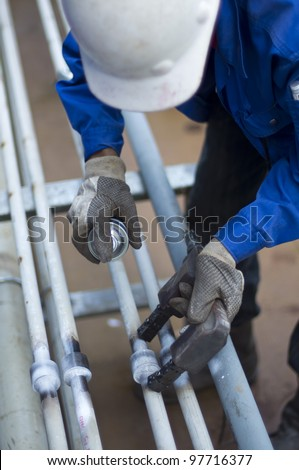 "worker with personal protective equipment checking the quality of weld joint on pipeline using Magnetic Particle Inspection ""MPI"" method - stock photo"