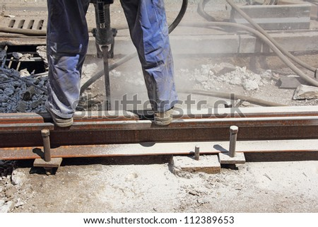 Worker with pneumatic hammer drill equipment breaking asphalt at construction site - stock photo