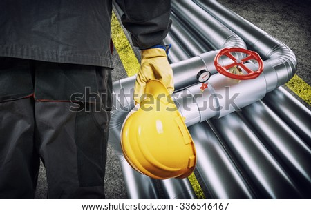 worker with protective gloves and helmet in front of industrial refinery oil pipes - stock photo