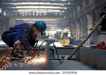 worker with protective mask welding metal and sparks - stock photo
