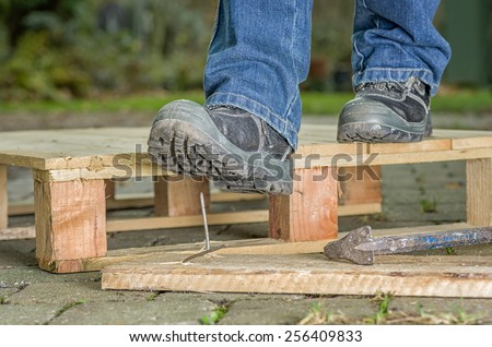 Worker with safety boots steps on a nail - stock photo