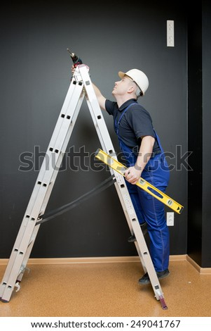 worker with tools, stands on a ladder - stock photo