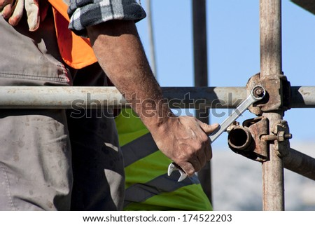 Worker with wrench in his hand builds iron scaffold on construction site  - stock photo