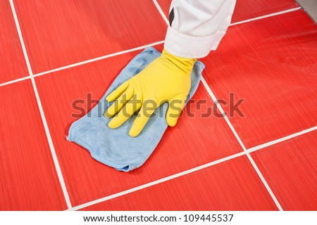 Worker with yellow gloves and blue towel clean red tiles grout from cement milk after grouting - stock photo