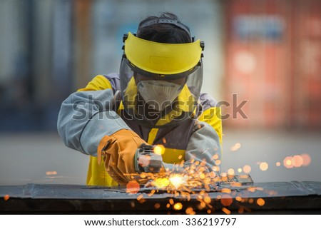 Worker work hard with the Electric wheel grinding on steel structure in factory - stock photo