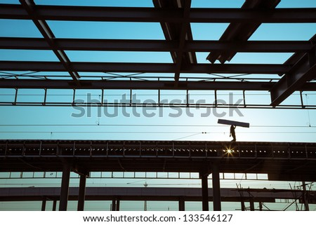 worker working in roof near sunset - stock photo