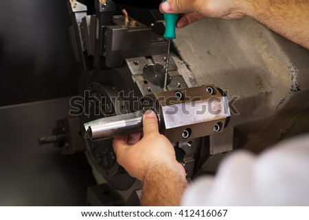 Worker working with cnc machine at workshop - stock photo