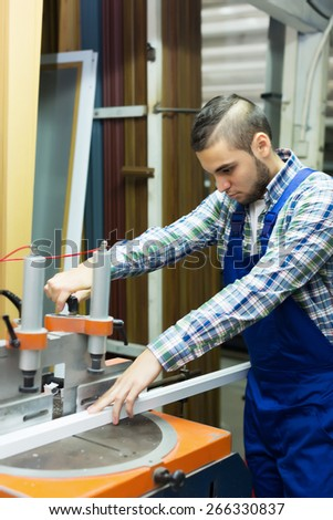 Worker working with PVC  on a machine at factory - stock photo
