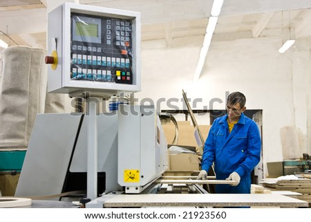 Worker working with wood paneling machine - stock photo