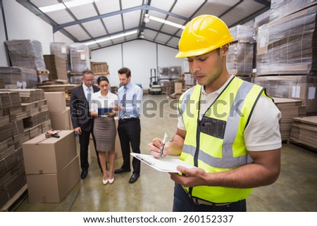 Worker writing on clipboard in front of his colleagues in a large warehouse - stock photo
