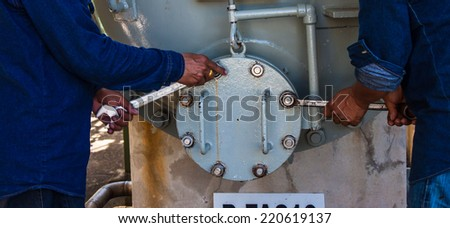 Workers are closed tank - stock photo