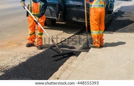 Workers are leveling asphalt on construction site road repair - stock photo
