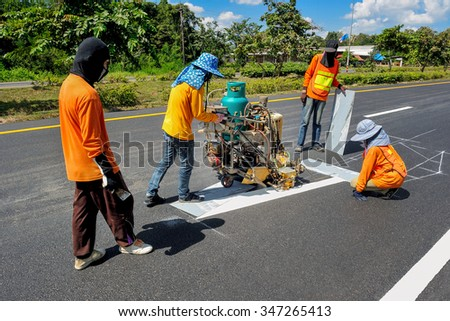 Workers are painted traffic lines with spraying machines. - stock photo
