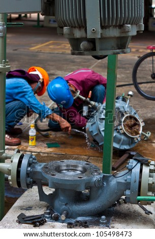 workers are repairing sundyne  pump in petrochemical plant - stock photo