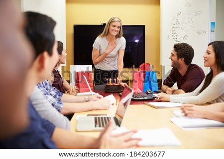 Workers Celebrating Colleague's Birthday In Office - stock photo