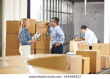 Workers Checking Goods On Belt In Distribution Warehouse - stock photo