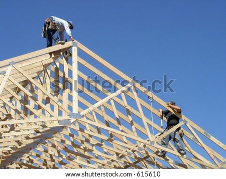 workers framing roof of a building - stock photo
