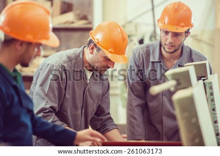 Workers in industrial cutting wood factory - stock photo