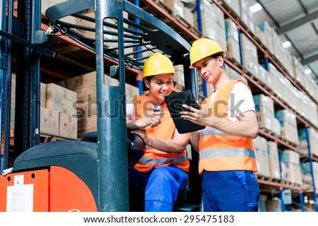 Workers in logistics warehouse at forklift checking list - stock photo