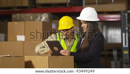 Workers in warehouse use digital tablet - stock photo
