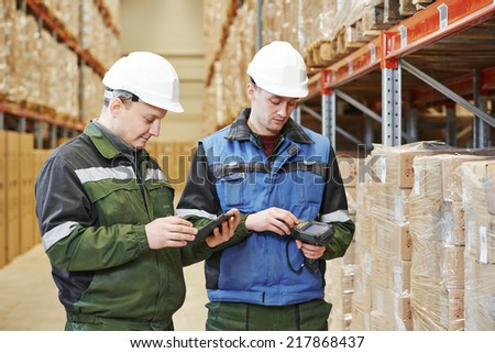 workers in warehouse with bar code scanner and tablet computer - stock photo