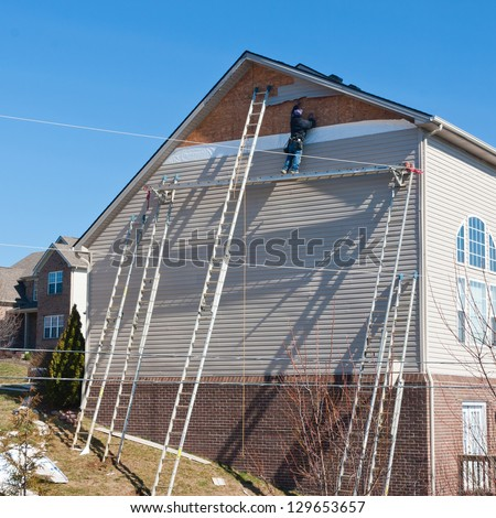 Workers installing plastic siding panels on two story house. - stock photo