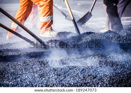 Workers making asphalt with shovels at road constructio - stock photo