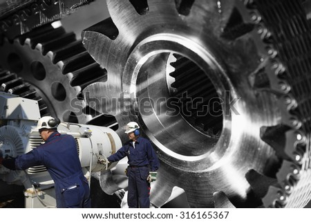 workers, mechanics with large cogwheels machinery, titanium and steel parts - stock photo