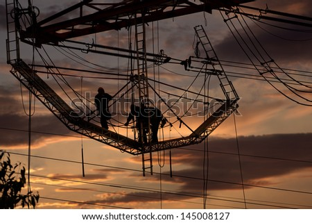 Workers on a highvoltage tower at sunset - stock photo