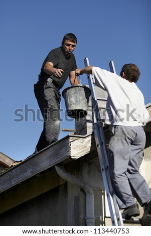 Workers on a roof - stock photo